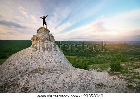 Man on peak of mountain. Emotional scene. - stock photo