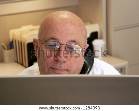 Man on phone looking over monitor - stock photo