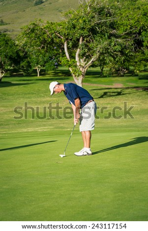 Man on putting golf putting green about to strike golf ball with - stock photo