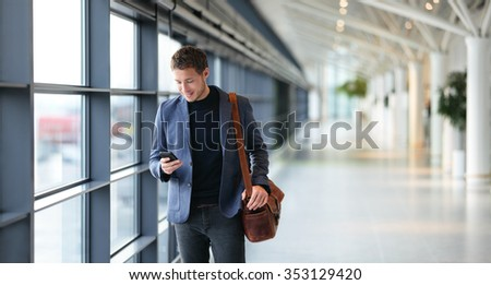 Man on smart phone - young businessman in airport. Casual urban professional business man using smartphone smiling happy inside office building. Handsome man wearing suit jacket indoors. - stock photo