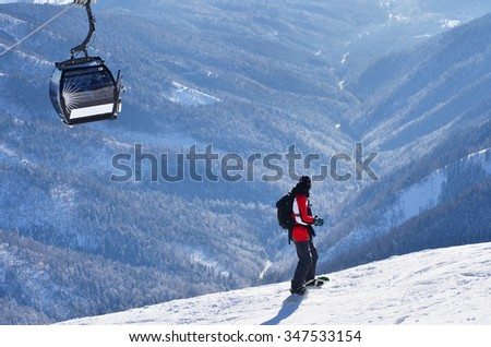 Man on snowboard during sunny winter active day in mountains over chairlift in mountains resort - stock photo