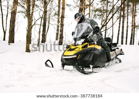 man on snowmobile in the winter forest