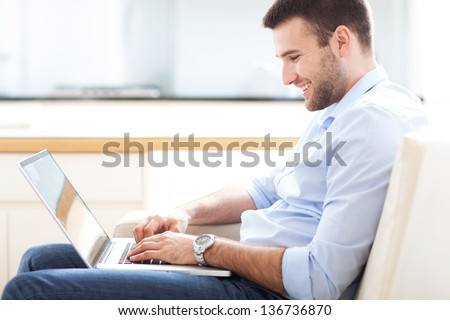 Man on sofa with laptop - stock photo