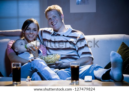 Man on sofa with woman feeding baby and holding a bowl of popcorn