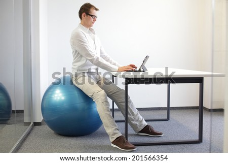 man on stability ball working with tablet - correct sitting position at workstation - office occupational disease prevention - stock photo