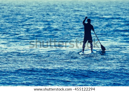 Man on Stand Up Paddle Board surrounded by sea water.