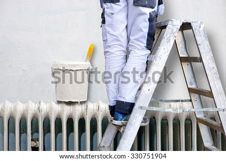 Man on stepladder painting wall. Plastic jar with white paint and paintbrush on radiator.
