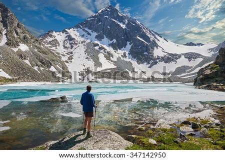Man on the background of a mountain lake. Russia, Siberia, Altai mountains, Katun ridge. - stock photo