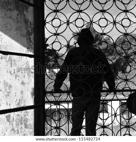 Man on the balcony of an abandoned house, metal door pattern. Black and white. - stock photo