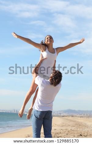 Man on the beach raising his beautiful girlfriend - stock photo