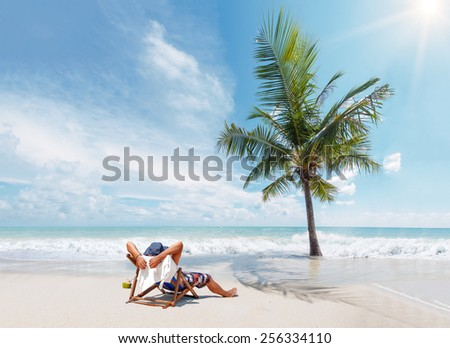 Man on the beach suntanning  - stock photo