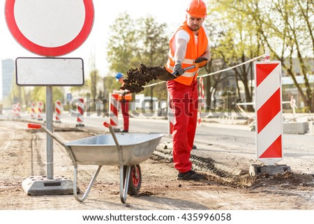 Man on the building site loading a wheelbarrow - stock photo