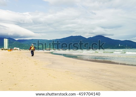 Man on the China Beach in Danang in Vietnam. It is also called Non Nuoc Beach. South China Sea and Marble Mountains on the background.