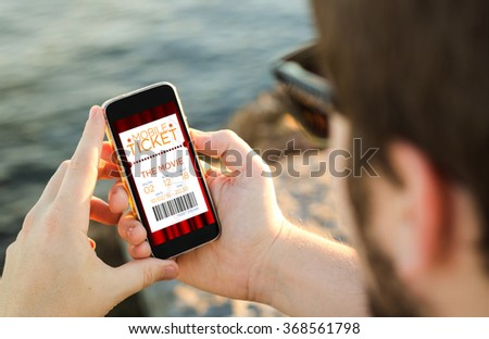 man on the coast using his smartphone to buy cinema tickets. All screen graphics are made up. - stock photo