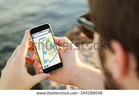 man on the coast using his smartphone to plan a route. All screen graphics are made up. - stock photo