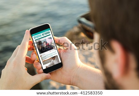 man on the coast using his smartphoneshowing social network. All screen graphics are made up. - stock photo