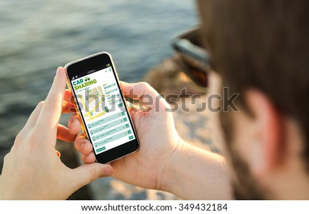 man on the coast with car sharing app on his smartphone . All screen graphics are made up. - stock photo