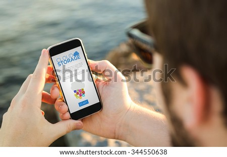 man on the coast with cloud storage on his smartphone . All screen graphics are made up.