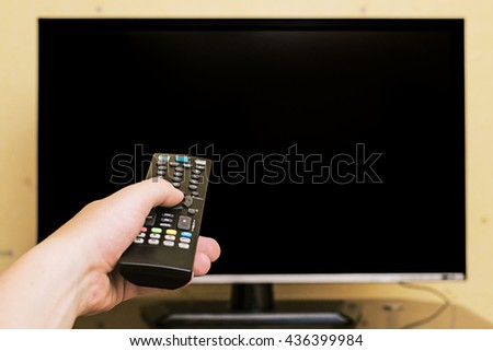 man on the couch watching tv and changing channels, hold and using remote controller, Hand  holding TV remote control with a television as background - stock photo