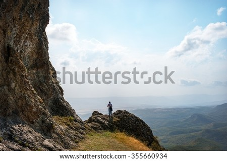 man on the edge of a cliff in the mountains