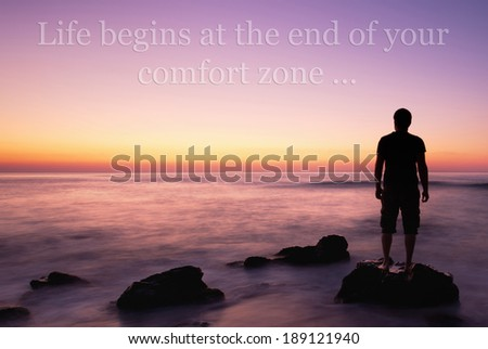 man on the edge on rock in calm sea sunrise, unknown inspirational quote above - stock photo
