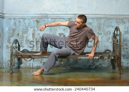 Man on the metal rusty bed in prison - stock photo