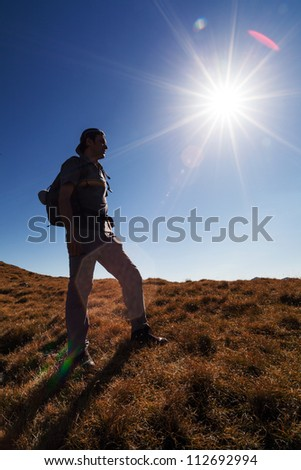 Man on the mountain with sun in frame - stock photo