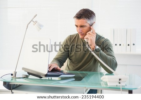 Man on the phone and using laptop in his office
