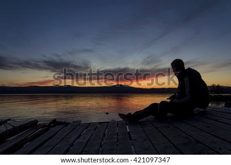 Man on the pier watching the beautiful sunset