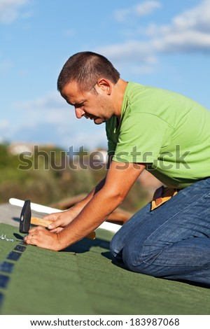 Man on the roof fastening bitumen roof shingles using nails and hammer - stock photo