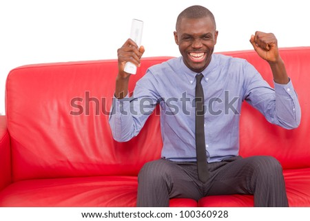 man on the sofa with remote control rejoice - stock photo