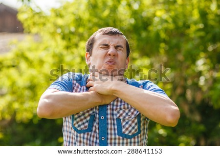 Man on the street choking himself hands on a green background leaves summer
