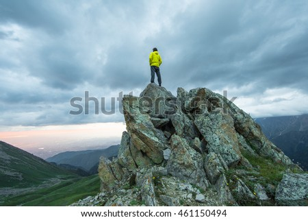 man on top of a mountain at sunset in summer