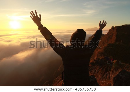 Man on top of mountain in fog. Conceptual design.low key lighting .Silhouette .Selective focus.Lens Flare. - stock photo