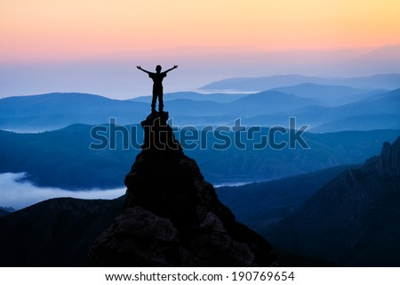 man on top of the mountain looking to the sun