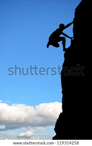 man on top of the mountain reaches for the sun - stock photo