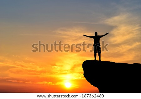 man on top of the mountain reaches for the sun