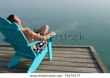 man on vacation relaxing at the end of the dock in Adirondack chair with ocean views - stock photo