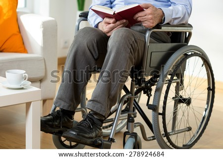 Man on wheelchair reading a book, horizontal - stock photo