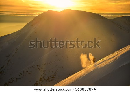Man on winter touristic trip under mountains playing with snow during calm sunset - stock photo