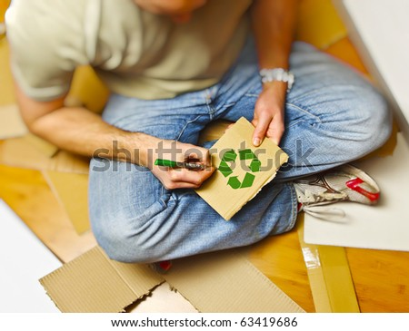 man on wood floor draw recycling symbol on cardboard - stock photo