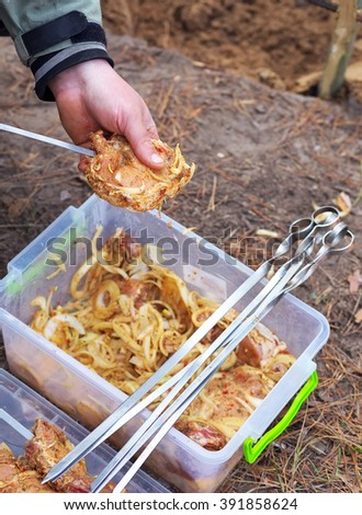 Man one hand holding the meat, other - stringing skewer. Stringing meat on a skewer in nature. Camping - stock photo
