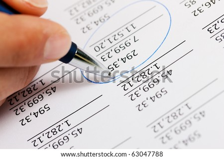 Man (only hand to be seen, presumably an accountant) working on a document with numbers