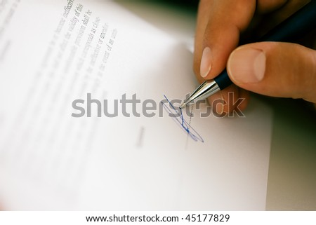 Man (only hand to be seen) signing a contract or another document (fake signature, focus on pen) - stock photo