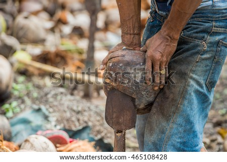 Man open coconut shell by old knife
