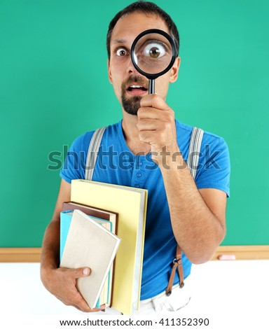 Man open-eyed with magnifier, among the books. Photo of smiling teacher, creative concept with Back to school theme - stock photo