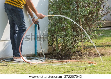 man open faucet with rubber tube in home garden
