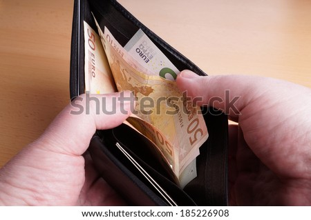 man opening black leather wallet full of euro bank notes - stock photo