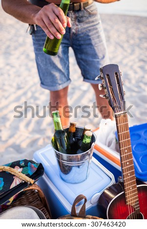 Man opening bottle of beer on the beach.  Depth of field, selective focus - stock photo
