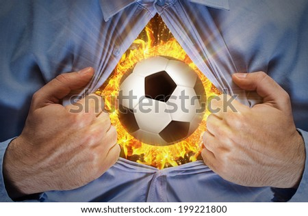 Man opening his blue shirt and showing ball inside his chest - stock photo